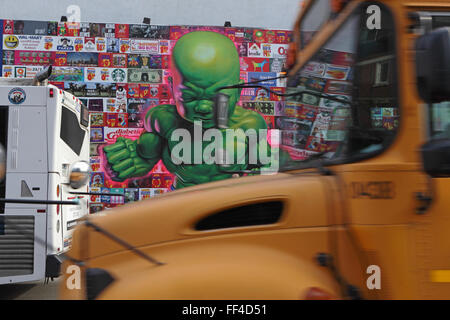 Ein gelber Schulbus fährt vorbei eine Collage von Ron English an der Bowery Wandbild Wand auf der Houston Street - Stockfoto