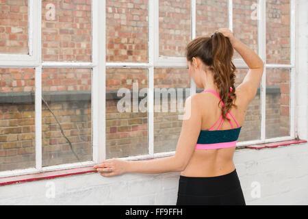 Frau, die aus einem Fenster in ein Fitness-Studio nach Training und Ausbildung - Stockfoto