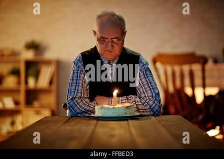 Reifer Mann Geburtstagskuchen mit einer Kerze zu betrachten - Stockfoto