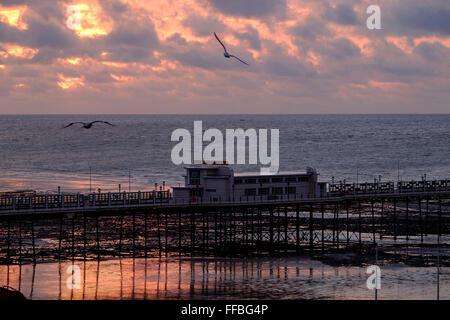 Worthing, Sussex, UK. 12. Februar 2016. UK-Wetter: Die Sonne geht hinter dem Pier in Worthing, UK, 02.12.2016. Bildnachweis: - Stockfoto