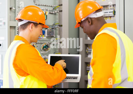 moderne Elektro-Ingenieure mit Laptop-Computer im Kontrollraum - Stockfoto