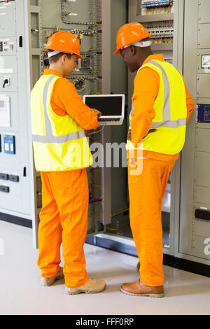 Heckansicht des erfolgreichen Techniker mit Laptop im Kontrollraum - Stockfoto