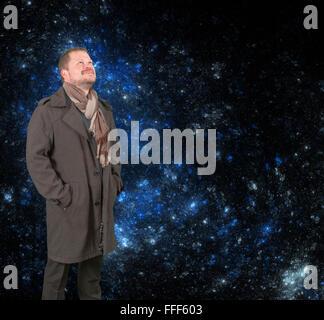 Mann mittleren Alters in einem Mantel und Schal auf Sternenhimmel Universum Hintergrund nachschlagen - Stockfoto