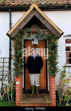 Älterer Mann, der in seiner eingerichtete Veranda, dass es für Weihnachten, Suffolk, England, UK - Stockfoto