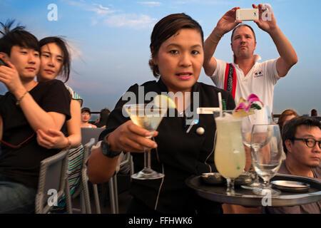 Kellnerin mit Cocktails in der Hand. Banyan Tree auf dem Dach Vertigo & Moon Bar, Restaurant, Bangkok, Thailand. - Stockfoto
