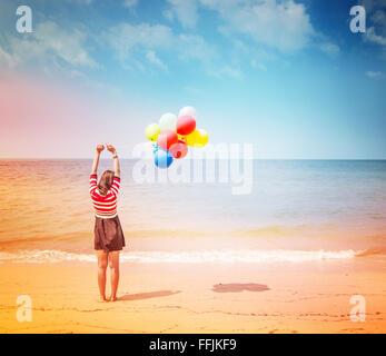 Frau mit bunten Luftballons am Strand, im freien Lebensstil Filter Bilder - Stockfoto