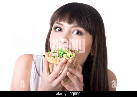 Junge schöne hungrigen Frau Essen sehr lecker Torte Kuchen mit Creme Gesicht bedeckt. Diät-Fehler-Konzept. Studio - Stockfoto