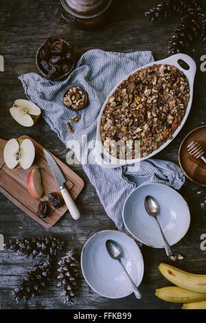 Gebackenes Haferflocken mit Datteln, Äpfel, Bananen und Walnuss ist frisch aus dem Ofen serviert und auf neu gewonnenem - Stockfoto