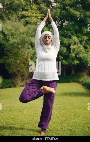 Muslimische Frau beim Yoga am Pool - Stockfoto