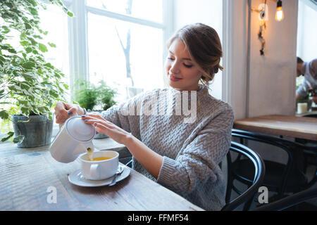 Glückliche Frau Tee im Café trinken