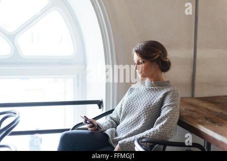 Junge schöne Frau mit Smartphone im café - Stockfoto
