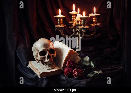 Stillleben mit Totenkopf, Buch und Kerze - Stockfoto