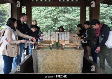 Besucher der Meiji-Schrein in Tokio, die sich durch Ausführen von Temizu auf eine Hand Waschbecken vor dem Betreten - Stockfoto
