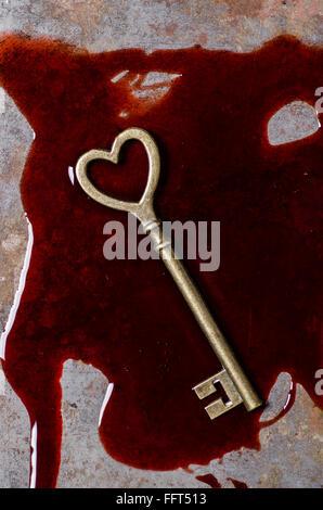 Schlüssel in einer Blutlache in Herzform - Stockfoto