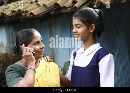 Mutter am Handy und Schule gehen Tochter vor Haus im Dorf, Maharashtra, Indien Model Release # 703Y und 703Z sprechen - Stockfoto