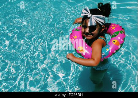 High Angle View Of Happy Girl Schwimmen im Pool mit Rettungsring - Stockfoto