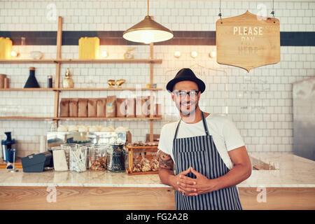 Porträt von glücklicher junge Mann trägt eine Schürze und Mütze stützte sich auf einen Café-Zähler. Männliche Barista - Stockfoto