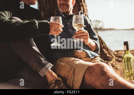 Bild der Reifen Liebespaar zusammen mit einem Glas Wein sitzen abgeschnitten. Mann und Frau, camping und hält ein Glas Wein.