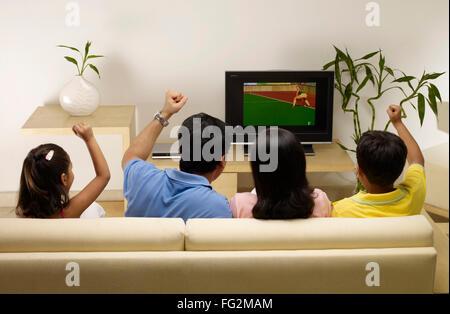 Kinder, deren Eltern jubeln beim beobachten Spiel im Fernsehen sitzen im Haus Herr #702R, Herr #702S, #702T Herr, - Stockfoto