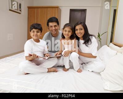 Eltern und Kinder mit Märchenbuch sitzt auf dem Bett im Schlafzimmer Herr #702R, Herr #702S, #702T Herr, Herr #702U - Stockfoto