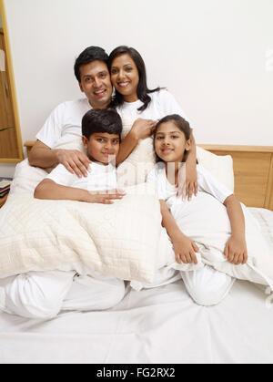 Kinder, deren Eltern halten Kissen sitzt auf dem Bett im Schlafzimmer Herr #702R, Herr #702S, #702T Herr, Herr #702U - Stockfoto
