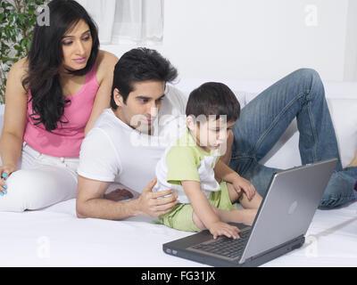 Paar mit einem Laptop mit ihrem Baby; HERR #779 L; HERR #779 M; HERR #779O - Stockfoto