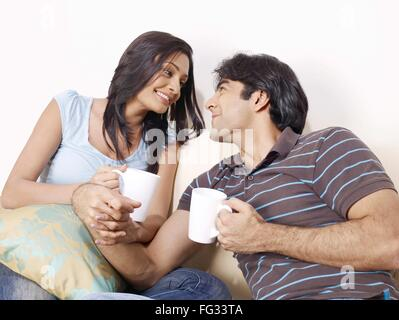 Junger Mann und Frau, die Hand in Hand Blick auf jedes andere Herr #702V, 702U - Stockfoto