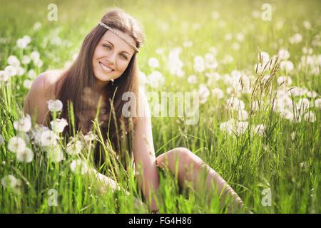 Schöne junge Frau lächelnd auf einer blühenden Wiese. Natur-Harmonie und Gelassenheit Stockfoto