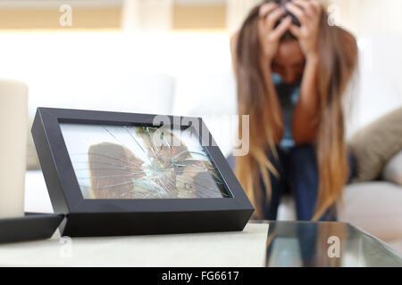 Traurig verzweifelt Frau oder Freundin nach einer Trennung in eine Couch zu Hause sitzen - Stockfoto