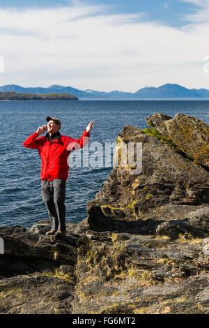 Man spricht auf seinem Smartphone an den felsigen Ufern des Tongass Narrows, Ketchikan, südöstlichen Alaska, Frühling - Stockfoto