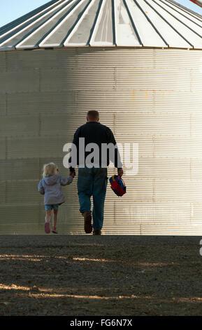 Landwirtschaft - ein Bauer und seine junge Tochter gehen Hand in Hand durch seinen Hof mit einem Silo im Hintergrund - Stockfoto