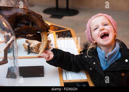 Jungen Schulalter Mädchen eine Smiladon Schädel Display Ausstellung Ausstellung zu berühren. Die Oxford University - Stockfoto
