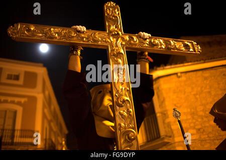 Eine vermummte Büßer hält ein goldenes Kreuz während einer Prozession der Karwoche in Trujillo, Extremadura, Spanien. - Stockfoto