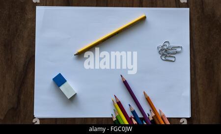 High Angle View Of bunte Bleistifte mit Radiergummi und Büroklammern auf Papier - Stockfoto