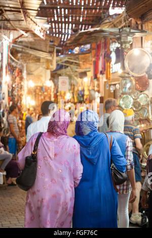 Zwei marokkanische muslimische Frauen tragen die traditionelle Kleidung einkaufen in der Suk /medina von Marrakesch. - Stockfoto