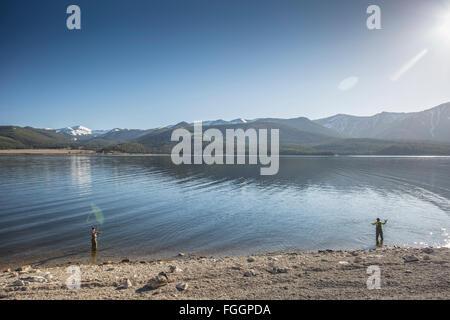 Zwei Frauen vom Ufer beim Fliegenfischen auf Montanas Hebgen Lake gegossen. - Stockfoto
