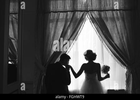 Braut und Bräutigam stehen vor Fenster - Stockfoto