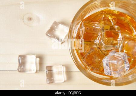 Glas Whiskey mit Eis auf Holztisch. Ansicht von oben - Stockfoto