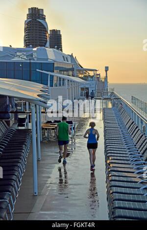 Cruise Liner Schiffsplattform am frühen Morgen Jogger läuft mit entlang Stromkreis zwischen Sonnenliegen nach über - Stockfoto