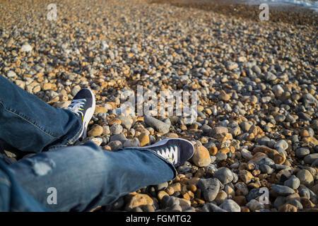 Beine einer Frau in Jeans sitzen am Strand von Brighton, UK - Stockfoto