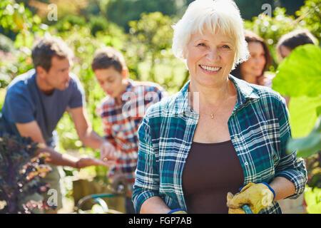 Lächelnde senior Porträt Frau im sonnigen Garten mit Familie - Stockfoto