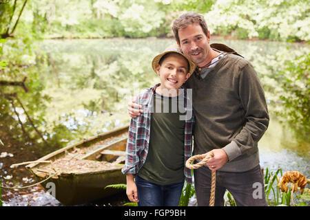 Porträt-Vater und Sohn mit Boot am Teich - Stockfoto