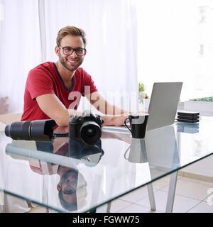 Quadratische Schuss eines jungen Fotografen lächelnd in die Kamera - Stockfoto