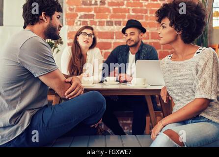 Gruppe junger Freunde sitzen und reden in einem Café. Junge Männer und Frauen in einem Café zu treffen und zu diskutieren. - Stockfoto