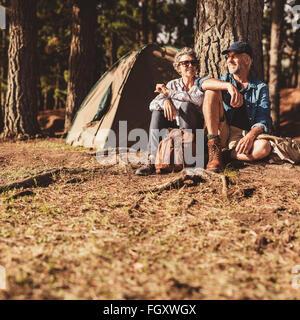 Porträt von glücklich älteres paar beisammen sitzen unter einem Baum im Wald. Ältere Mann und Frau entspannend auf - Stockfoto