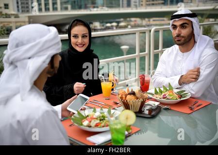 Junge Emiratis arabische Freunde Essen in einem restaurant - Stockfoto