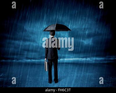 Geschäftsmann, stehen im Regen mit Regenschirm - Stockfoto