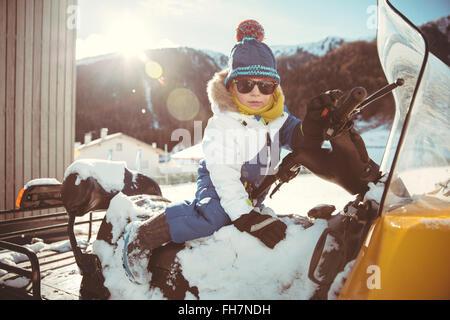 Italien, Val Venosta, Slingia, junge mit Sonnenbrille sitzt auf einem Schneemobil - Stockfoto