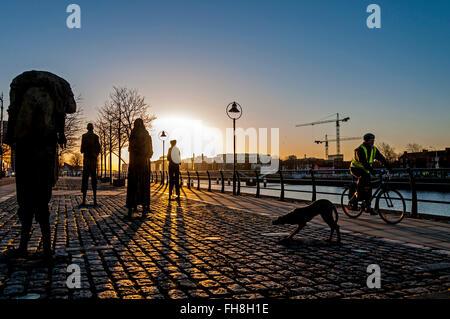 Famine Memorial, Dublin, Irland, ein Mann Zyklen vorbei bei Sonnenaufgang am Morgen - Stockfoto