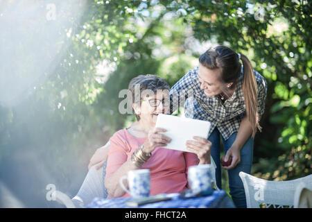 Großmutter und Enkelin im Garten zusammen mit Blick auf digital-Tablette - Stockfoto